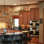 Kitchen with stone hood, granite countertops, pendant lighting and crown molding - Anthony Thomas Builders