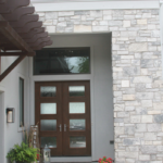 Stone entrance with wood trellis - Anthony Thomas Builders