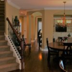 Dining room with iron rail staircase and arches - Anthony Thomas Builders