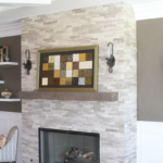 Living Room with wainscoting and stone veneer dry stacked fireplace and mantle with beam - Anthony Thomas Builders