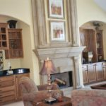 Great Room with vaulted ceilings, arches, built-ins and precast stone fireplace - Anthony Thomas Builders