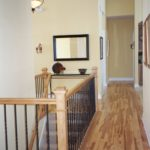 Hallway with wrought iron railing - Anthony Thomas Builders