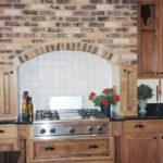 Kitchen with brick hood alcove and tile backsplash - Anthony Thomas Builders