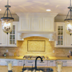 Kitchen with granite countertops, cooktop and crown molding - Anthony Thomas Builders