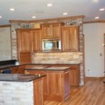 Kitchen with open concept , island and brick backsplash - Anthony Thomas Builders