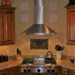 Kitchen with granite countertops and stainless steel hood - Anthony Thomas Builders
