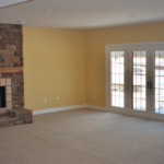 Lower level with walk out and cultured stone stepped marble fireplace - Anthony Thomas Builders